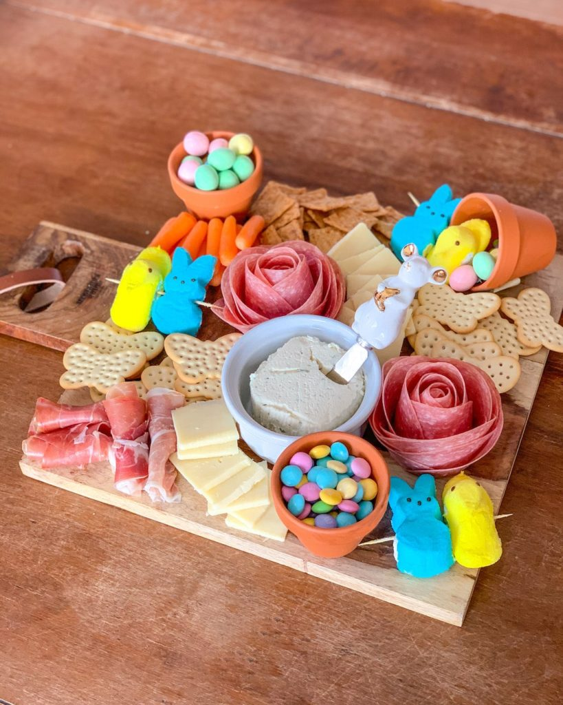 Easter charcuterie board with salami roses, butterfly crackers, Easter candy, Peeps and more