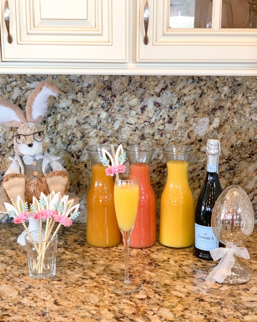 Easter mimosa brunch with juices, prosecco, bunny straws and Easter decor